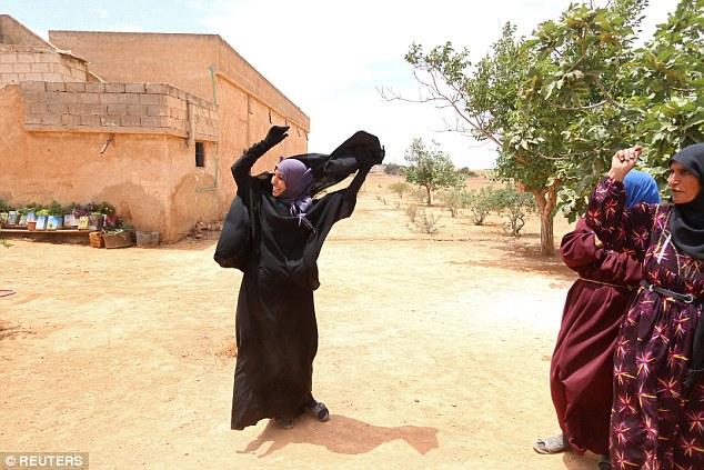 Una mujer saca un niqab que llevaba bajo el gobierno de ISIS en su pueblo después de Fuerzas Democráticas Siria (SDF) tomó el control de la misma, en las afueras de la ciudad Manbij, Siria, el 9 de junio