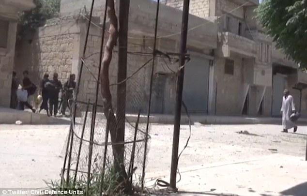 El video también mostró los hombres, las mujeres y los niños corriendo a la seguridad a través de las calles destrozadas de Manbij