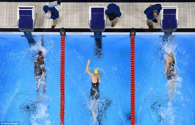 Simone Manuel of the United States touches the wall to win gold in the Women's 100m Freestyle Final at the same time as Canada's Penny Oleksiak
