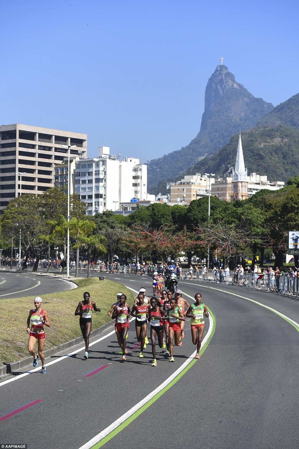 Competitors are seen running past Corcovado and the Christ the Redeemer statue during the Women's Marathon