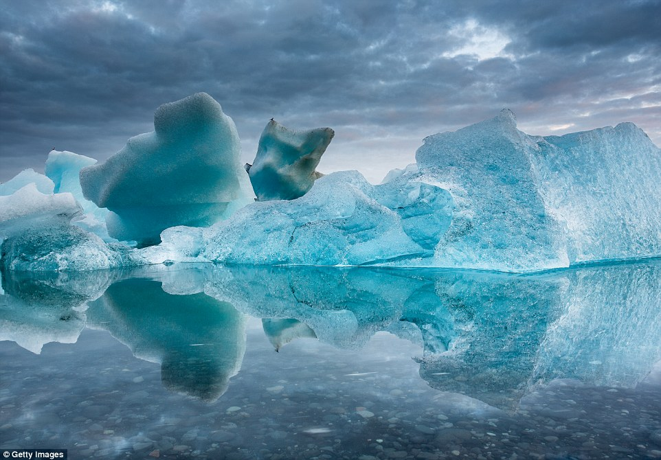 Icebergs melt on a midsummer night at Jökulsárlón in Iceland, looming over crystal-clear water, under a tempestous sky