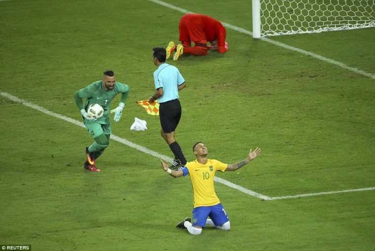 Goalkeeper Weverton races towards Neymar who sinks to his knees after he won the gold medal for Brazil