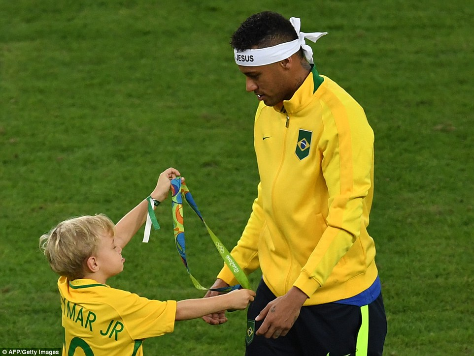 Neymar walks on the pitch with his young son who holds his father's gold medal in his hands