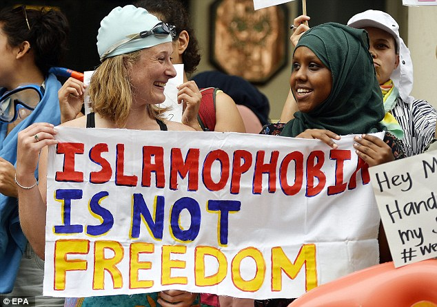 A woman holds up a sign saying 'Islamophobia is not freedom' at a burkini protest
