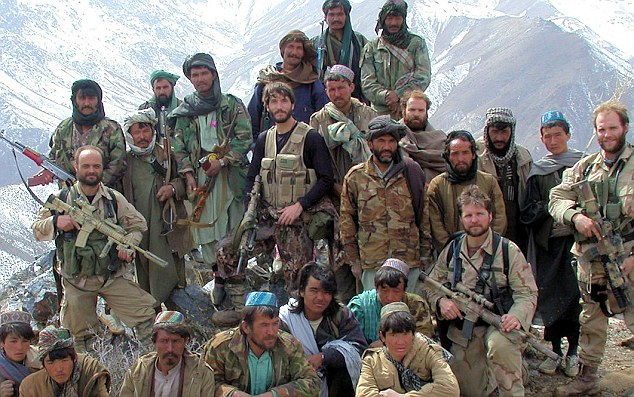 Chapman (seen kneeling on one knee fourth from the right) is photographed with US and Afghan fighters