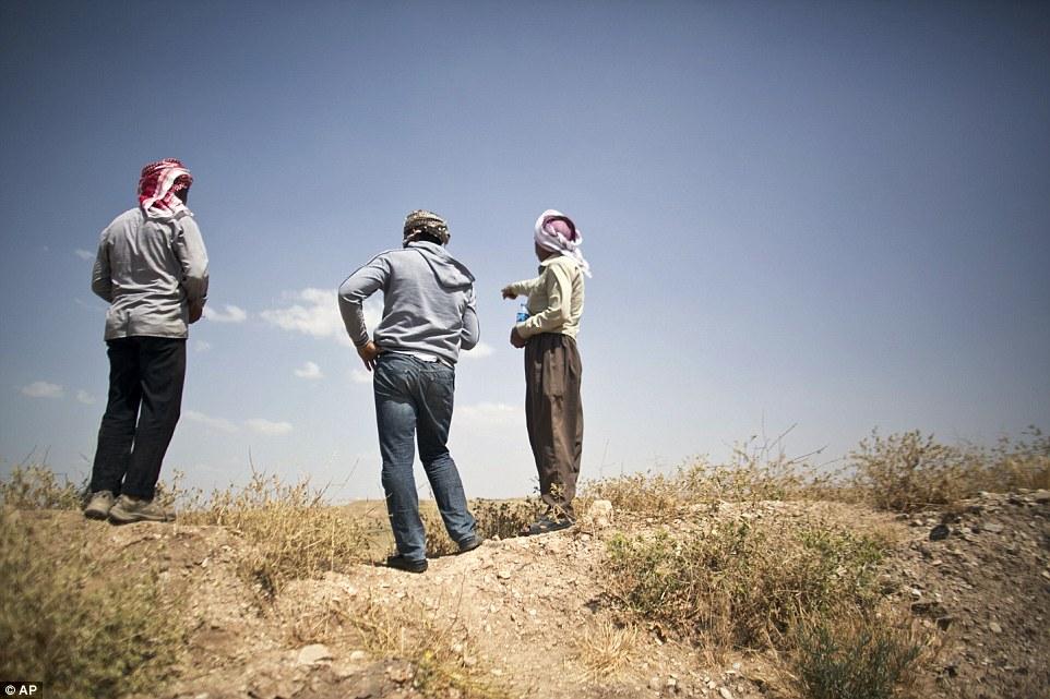 Arkan Qassim (centro) se ve en el sitio donde fue testigo de las docenas de muerte de los hombres yazidi en 2014 agosto en Hardan, el norte de Irak