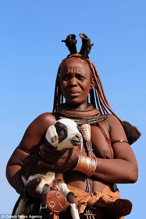A member of the Himba tribe pictured holding a baby goat