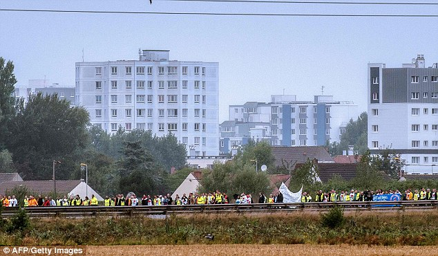 A medida que la cadena humana bloqueó la calzada, los manifestantes agitaban pancartas contra el campamento de la selva
