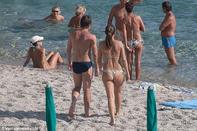 The former Italy boss and his wifeElisabetta Muscarello make their way towards the sea