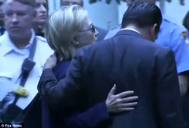 One of Clinton's handlers is seen with his arm across her shoulders. She is seen with her arm resting on his back as she leaves the ceremony
