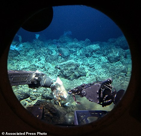 Robotic arms on the Pisces V submersible open a bag of bait