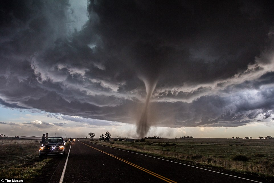 Overall Winner: An apocalyptic tornado near the town of Wray, Colorado, taken by Tim Moxon. He said: 'We were among a number of people, including those you see in the shot, nervously enjoying the epic display nature put on for us'