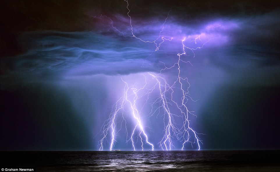 The Guanabura oil tanker being hit by lightning, taken by Graham Newman. He says: 'Shortly after taking the shot, the lightning cell closed on my position on the beach and I grabbed up my equipment and ran for my life'