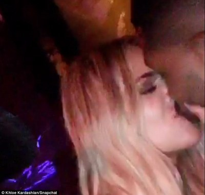 It's official! Khloe Kardashian shares a romantic kiss with her new man Tristan Thompson backstage at a Kanye West concert in Miami on Friday night