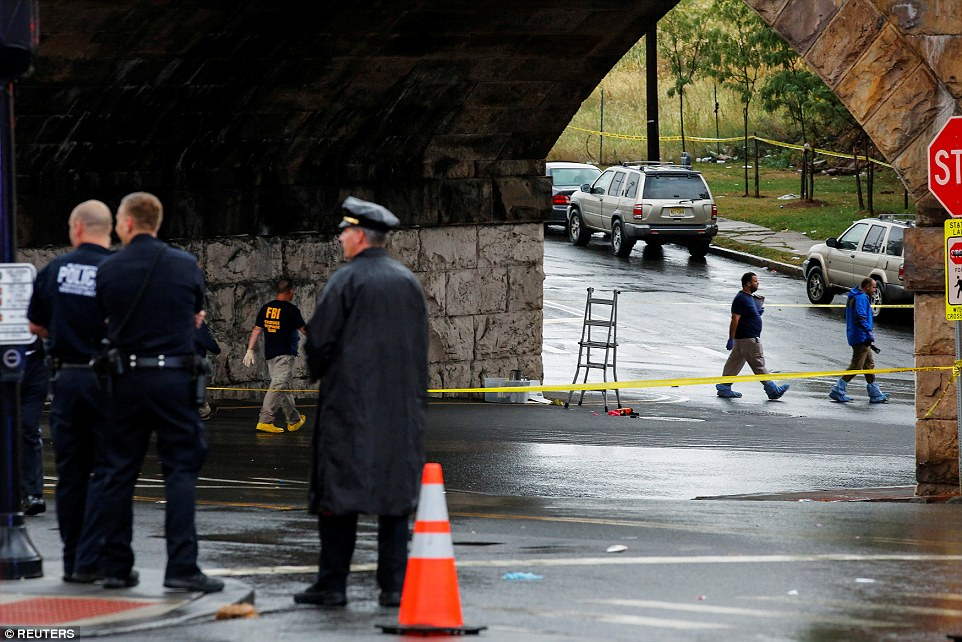 FBI officials and police officers walk near the area where an explosive device left at a train station was detonated by the authorities in Elizabeth, New Jersey on Monday