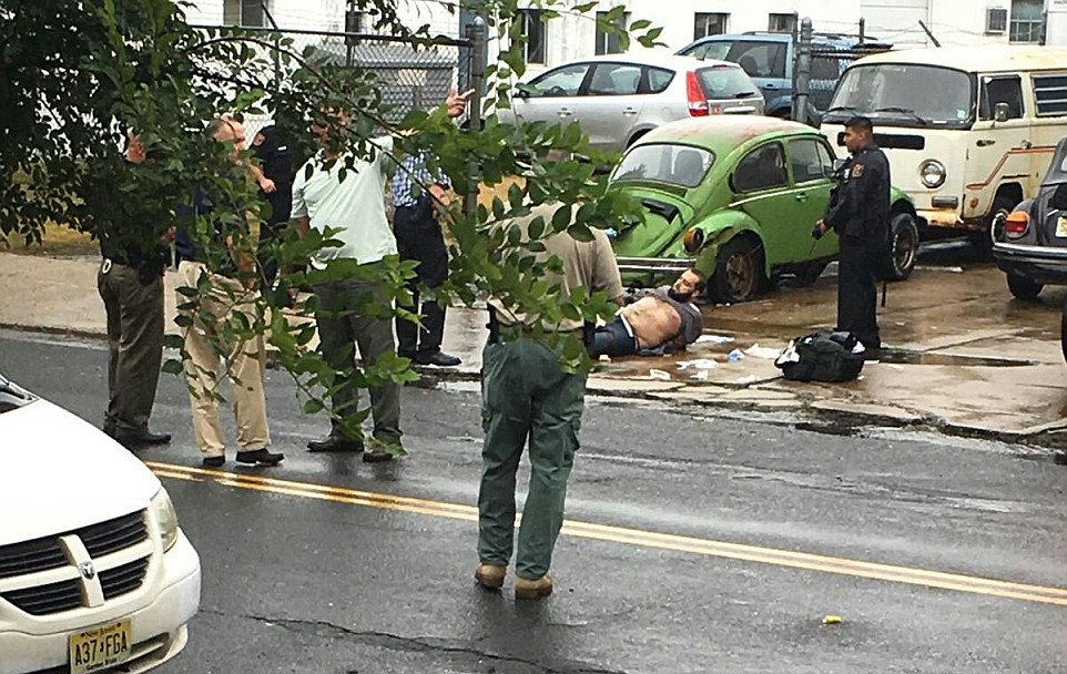 Ahmad Khan Rahami has been taken into custody after a shootout with police in Linden, New Jersey Monday morning. Rahami is picture laying on the ground with his hands restrained behind his back above