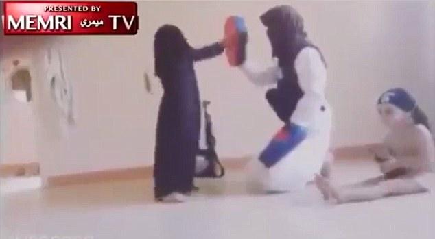 Video, capturado en un lugar desconocido, muestra a una muchacha vestida con un burka de pie junto a una ametralladora y puñetazos repetidamente almohadillas de entrenamiento normalmente utilizado por los boxeadores