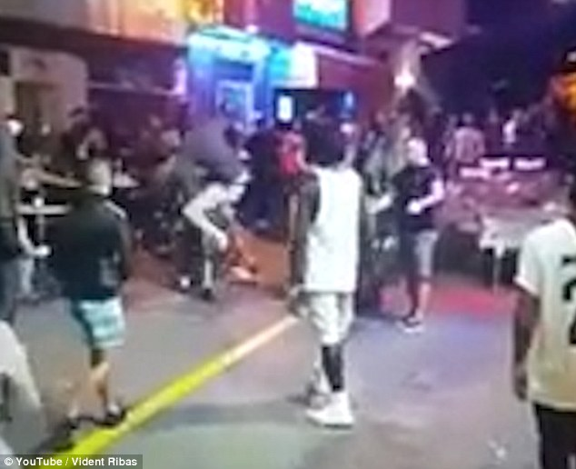 Violence: Another attacker wearing white trousers launches a flying kick at his victim (centre)