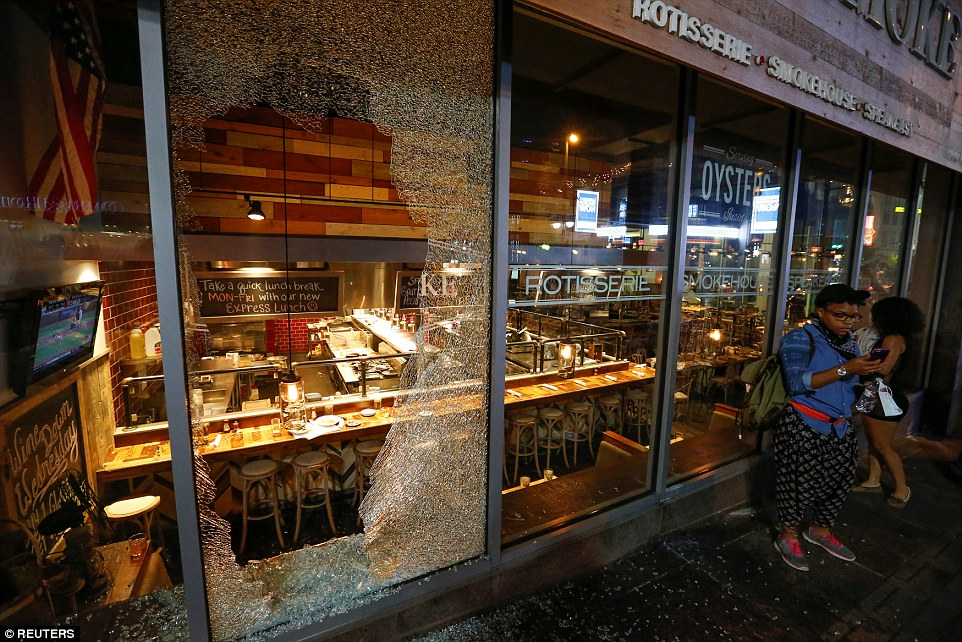 A window at the restaurant City Smoke is smashed in uptown Charlotte during the protests