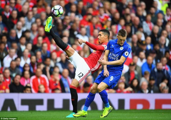 United centre-half Chris Smalling clears the ball under pressure from Leicester striker Jamie Vardy