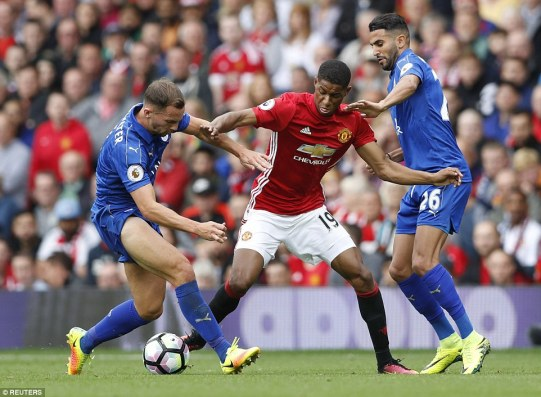 United's teenage striker Marcus Rashford attempts to hold off Leicester duo Danny Drinkwater (left) and Riyad Mahrez