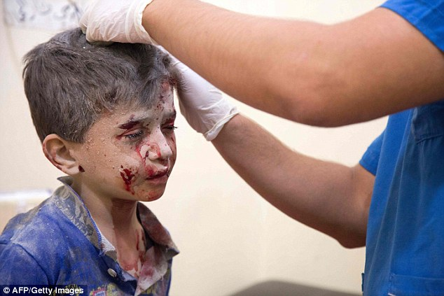 A young boy is treated for injuries as hostilities intensified on Friday night with the series of bombings