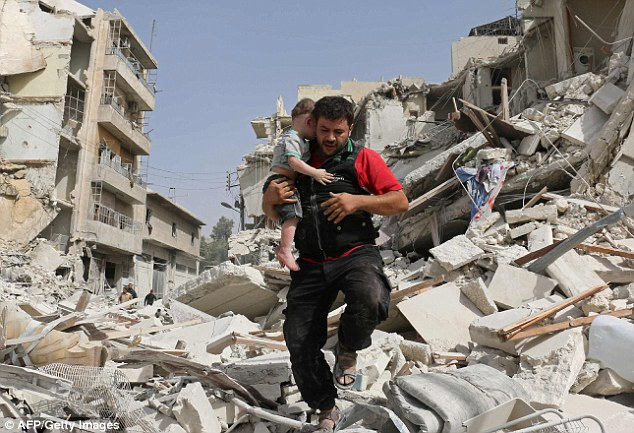 A man carries his child to safety after fresh bombardments that killed 25 people, according to The Syrian Observatory for Human Rights