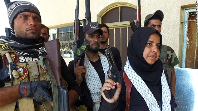 Um Hanadi holds a Beretta 9-millimeter pistol aloft in front of some of the men she commands