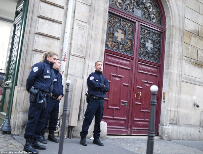 Police officers remain stationed at the apartment building in Paris where Kim Kardashian was robbed in a terrifying attack in the early hours of Monday morning