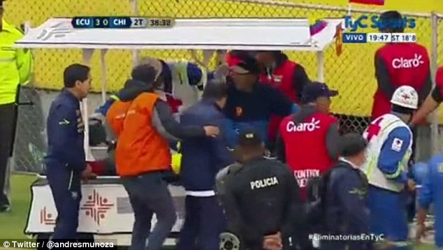Stewards and medical staff gather around Valencia as he receives treatment