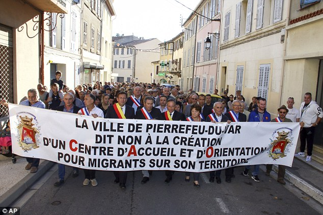 Residents hold a banner reading: 'City of Pierrefeu says no to the creation of a reception centre for migrants'