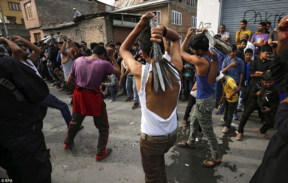 Crowds of people watch the Kashmiri Shiite Muslims carry out the ritual in the streets of Srinagar, India