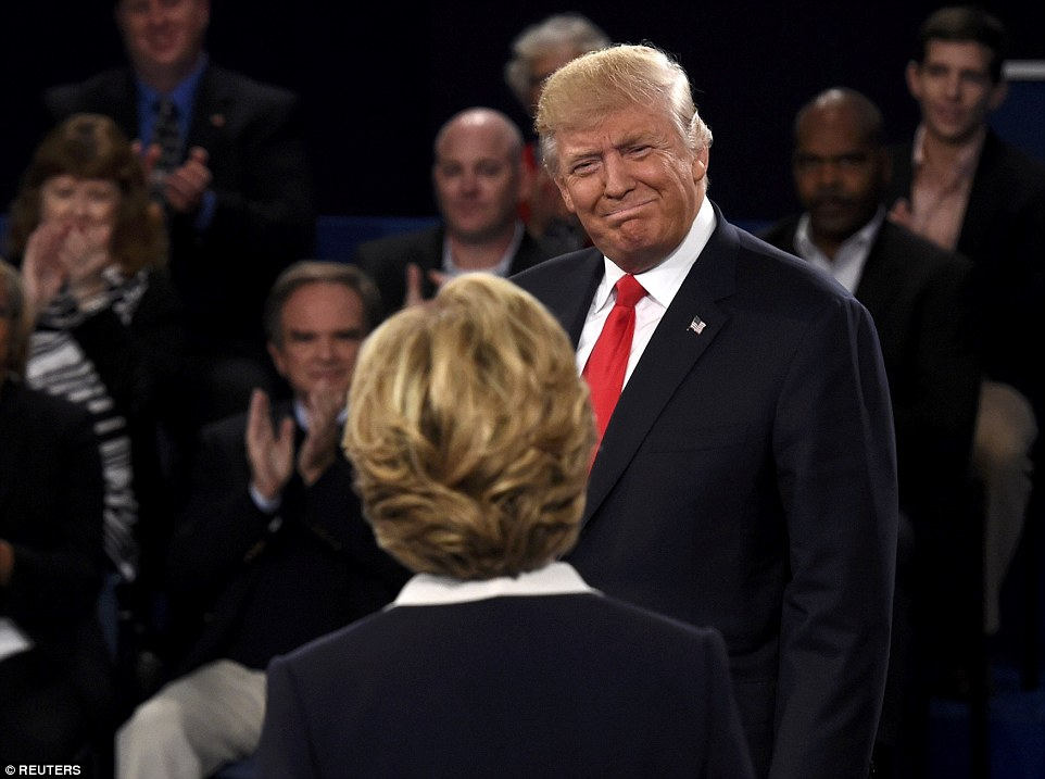 Republican presidential nominee Donald Trump smiles at Hillary Clinton as the two walked onto the stage at the start of the debate