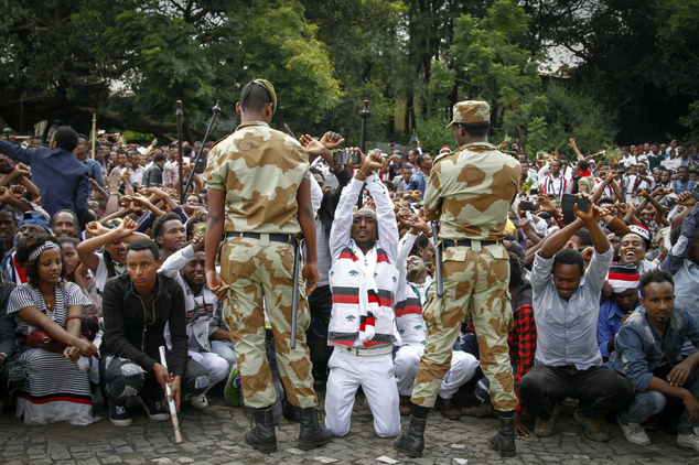 FILE - In this Sunday, Oct. 2, 2016 file photo, Ethiopian soldiers try to stop protesters in Bishoftu, in the Oromia region of Ethiopia. German Chancellor An...