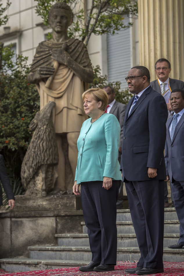 German Chancellor Angela Merkel, center, and Ethiopia's Prime Minister Hailemariam Desalegn, right, inspect the honor guard at the national palace in Addis A...