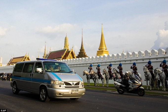 Saluted by a horseback honor guard, a van carrying the body of King Bhumibol Adulyadej arrives at Grand Palace