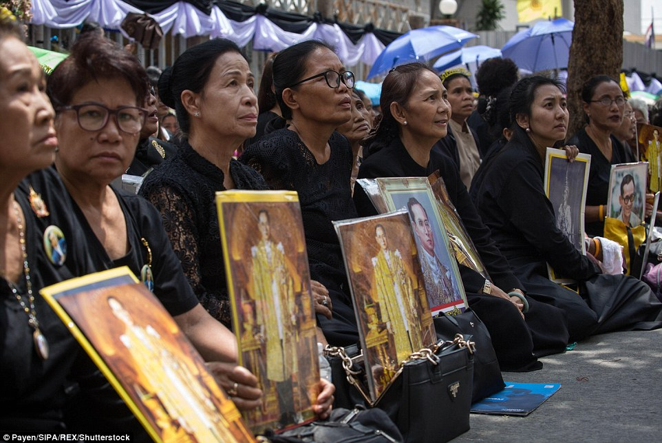 Women wearing black carry portraits of the late monarch, who many Thai people saw as a guarantor of political stability