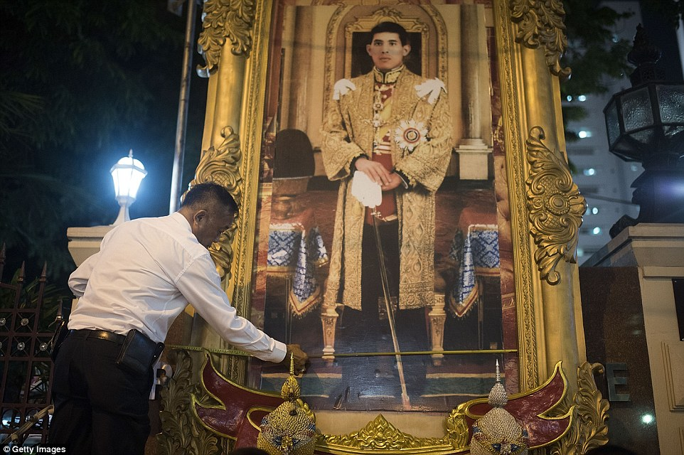 A Thai official measures the size of a frame at the Police Headquarters. The new portrait of Crown Prince Maha Vajiralongkorn, the heir to King Bhumibol, did not fit inside