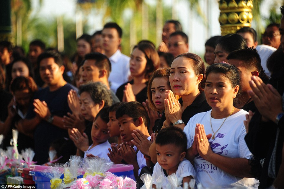 Mourners pray before offering alms to Buddhist monks during a ceremony to pay respects to the late Thai King