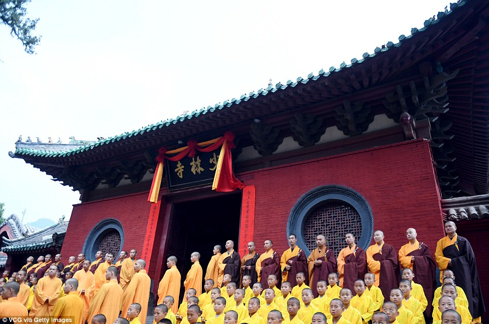 Chinese monks in traditional orange robes watch on outside a red temple as the competitors get ready for the event