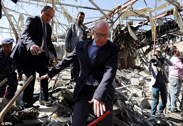 UN Humanitarian Coordinator in Yemen, Jamie McGoldrick, stumbles as he inspects the destroyed funeral hall, two days after an alleged Saudi-led airstrikes targeted it, in Sana'a