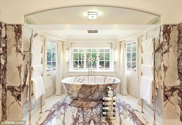 The bathroom, pictured, in the 24,000 sq ft house is made from 12 types of Italian marble