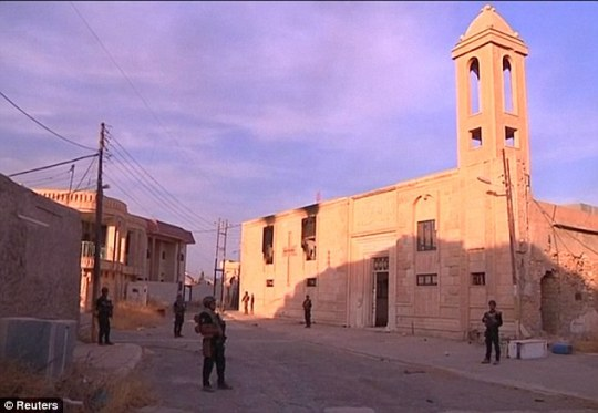 Iraqi forces surround a liberated church which had bee destroyed during the occupation of ISIS