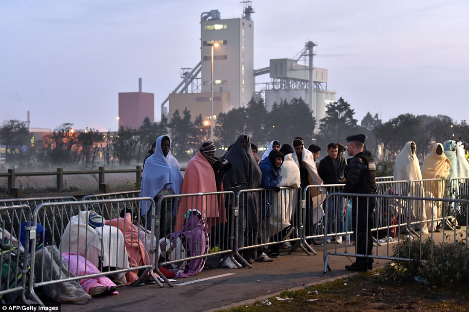 A French anti-riot police officer stands guard by migrants wrapped in blankets. Police in Calais have battled near-nightly attempts by migrants to reach Britain over the past year