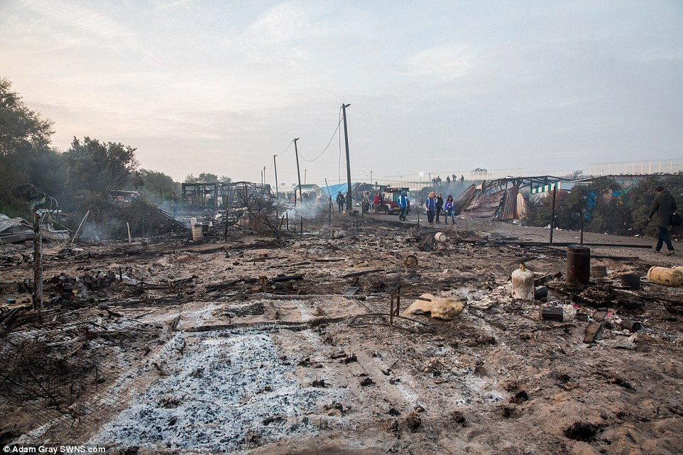 The main row of shops in the Calais Jungle are burnt to the ground as police suspect that migrants burnt them down in the night