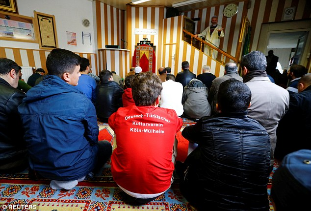 Young Muslims listen to a Turkish imam during Friday prayers at the Turkish Kuba Camii mosque