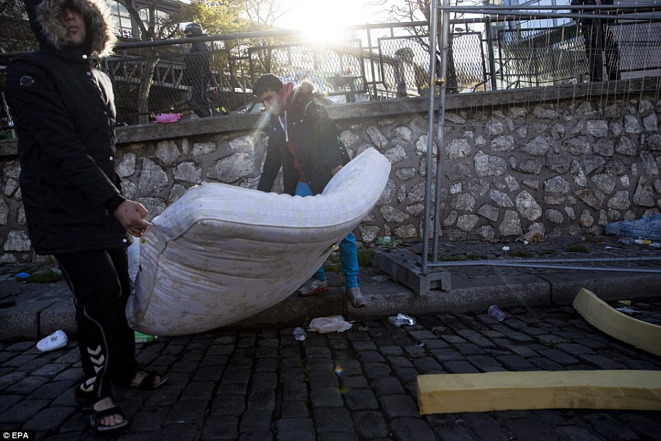 Two Afghan migrants remove their mattress after French police asked them to remove their makeshift camp