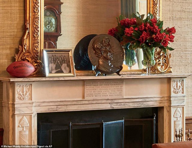 A look at the mantle, which holds fresh-cut flowers, a personalized football  and a giant plate with the likeness of Abraham Lincoln, who like Obama was from Illinois