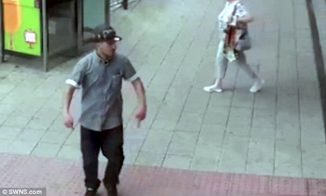 this is the moment a thug admired the reflection of his blood-splatted hands after stabbing a tram passenger in an unprovoked daylight attack (pictured)