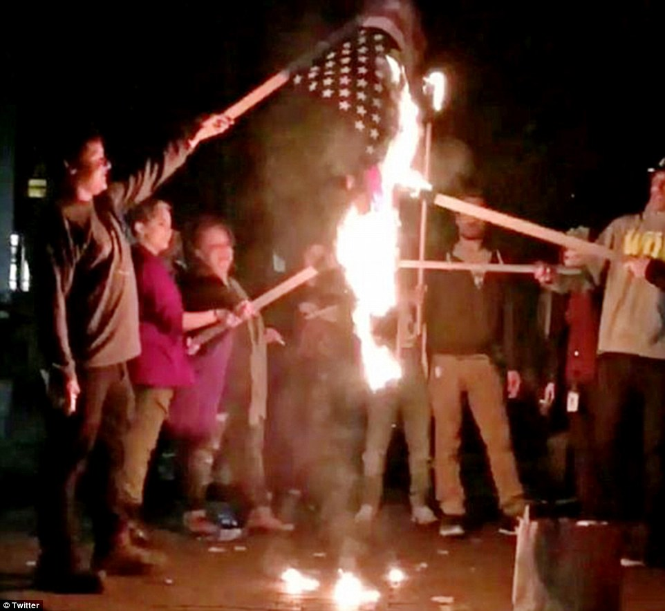 Portland: An American flag is set ablaze in the center of Portland, where dozens had gathered to block traffic and train lines
